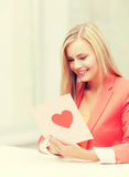 Woman holding postcard with heart shape Royalty Free Stock Photo
