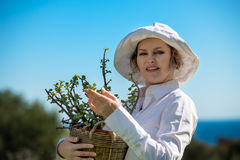 Woman holding a pot with plant. Woman in white holding a pot with plant with blue sky background Royalty Free Stock Photography