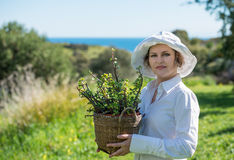 Woman  holding a pot with plant. Woman in white holding a pot with plant outdoors Royalty Free Stock Photo