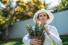 Woman holding a pot with plant. Woman in white holding a pot with plant outdoors Stock Images