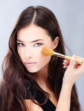 Woman holding powder brush. Portrait of a pretty young woman holding powder brush Royalty Free Stock Images