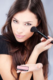 Woman holding powder brush. Pretty young woman holding powder brush Stock Image