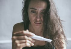 Woman is holding a pregnancy test with a depressed face expression stock photo