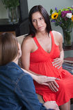 Woman Holding Pregnant Tummy. Young beautiful women relaxing on chair with friend holds her tummy Royalty Free Stock Images