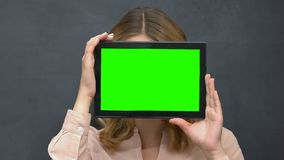 Woman holding prekeyed tablet, hiding face behind, place for advertisement stock video footage