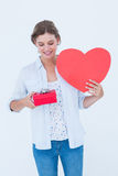 Woman holding a present and heart card. On white background Stock Photography