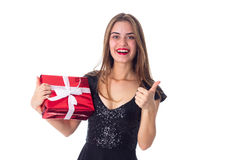 Woman holding a present and showing thumb up Royalty Free Stock Image