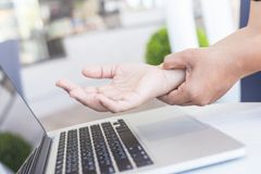 Woman holding and pressing or touching her wrist while working w Stock Photography