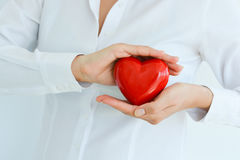 Woman holding and protecting a red heart shape Stock Photography