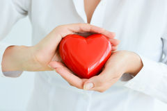 Woman holding and protecting a red heart shape Stock Image