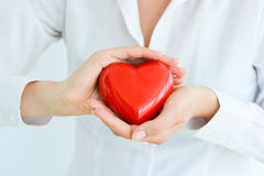 Woman holding and protecting a red heart shape Stock Photos