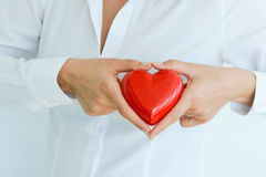 Woman holding and protecting a red heart shape Royalty Free Stock Image