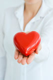 Woman holding and protecting a red heart shape Stock Photo
