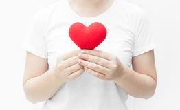Woman holding and protecting a red heart shape on white background close-up Stock Photos