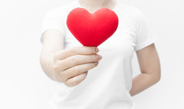 Woman holding and protecting a red heart shape on white background close-up Royalty Free Stock Photos