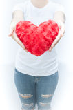 Woman holding and protecting a red heart shape on white background close-up Stock Photo