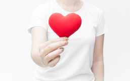 Woman holding and protecting a red heart shape on white background close-up Stock Image