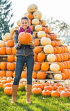 Woman holding pumpkin in front of pumpkin piramide Royalty Free Stock Photo