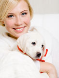 Woman holding puppy of labrador with red ribbon Stock Photo
