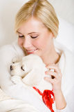 Woman holding puppy with red ribbon Royalty Free Stock Photography