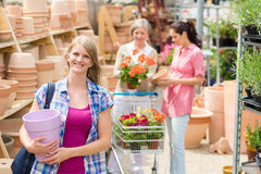 Woman holding purple pot in garden center Stock Images