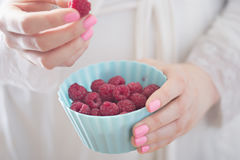 Woman holding raspberries in blue bowls. Woman with raspberries on white background Stock Photos