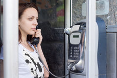 Woman holding the receiver in a telephone booth Stock Images