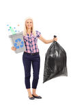 Woman holding a recycle bin and a trash bag Stock Images