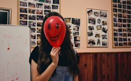 Woman Holding Red Balloon on Her Face Photo Inside Classroom Royalty Free Stock Photos