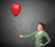 Woman holding a red balloon Stock Photo