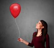 Woman holding a red balloon Stock Photos