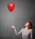 Woman holding a red balloon Stock Photography
