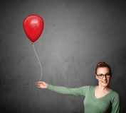 Woman holding a red balloon Royalty Free Stock Images