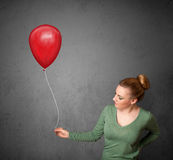 Woman holding a red balloon Royalty Free Stock Photo