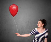 Woman holding a red balloon Stock Images