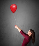 Woman holding a red balloon Royalty Free Stock Image