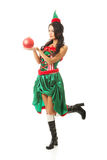 Woman holding red christmas bubble, wearing elf clothes, bending knee.  Royalty Free Stock Image