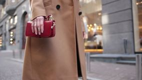 Woman holding red clutch while walking on street stock video footage