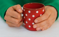 Woman holding a red coffee cup with white polka dots on a white table cloth. Delicate female hands of a woman in a bright green sweater holding an empty red stock image