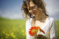 Woman holding red flowers in field. Royalty Free Stock Image