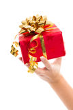 Woman is holding a red gift box with golden ribbon for christmas Stock Images