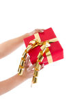 Woman is holding a red gift box with golden ribbon for christmas Royalty Free Stock Photo