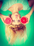 Woman holding red grapefruit having crazy windblown hair Stock Photos