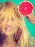 Woman holding red grapefruit having crazy windblown hair Royalty Free Stock Image