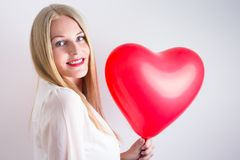 Woman holding a red heart balloon Stock Images