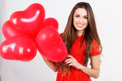 Woman holding red heart balloons Stock Photo