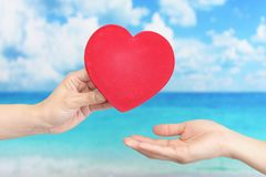A red heart love symbol. Woman holding a red heart love symbol stock photo