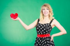 Woman holding red heart love symbol. Woman blonde cute girl wearing dotted dress holding red heart love symbol studio shot on green. Valentines day happiness royalty free stock photography