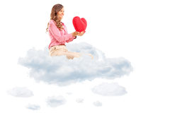 Woman holding a red heart seated in cloud. Isolated on white background Royalty Free Stock Photo