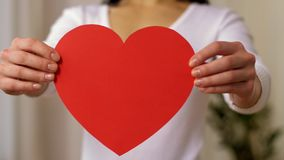 Woman holding red heart shape made of paper. Love, valentines day, charity and people concept - woman holding red heart shape made of paper stock video footage